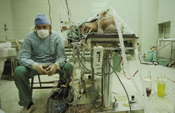 Cardiólogo después de realizar un transplante de corazón  por 23 horas continuas. Su ayudante está durmiendo en la esquina.